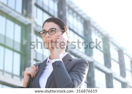Low angle view of businesswoman using cell phone outside office building - stock photo