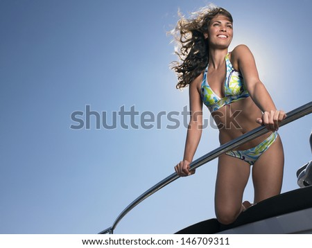 Low angle view of cheerful woman in bikini standing on yacht against blue sky - stock photo