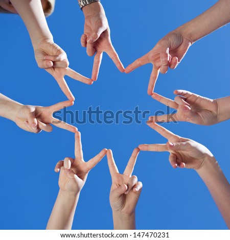 Low angle view of childrens hands forming a star with their fingers touching to the form the points against a clear blue sky, conceptual of teamwork and hope - stock photo
