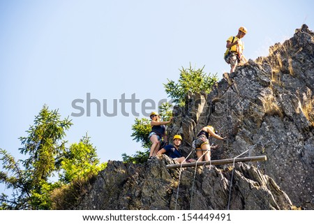 Low angle view of climbers climbing on rock - stock photo