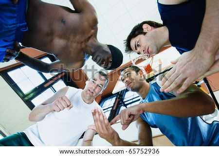 Low angle view of coach with basketball players in huddle - stock photo