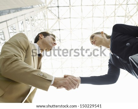 Low angle view of confident businessman and businesswoman shaking hands against ceiling - stock photo