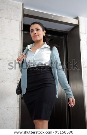 Low angle view of confident female entrepreneur stepping out of elevator - stock photo
