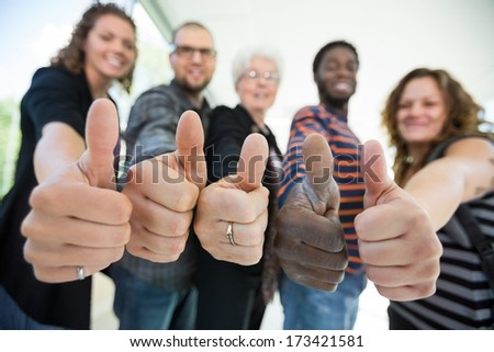Low angle view of confident multiethnic university students gesturing thumbsup