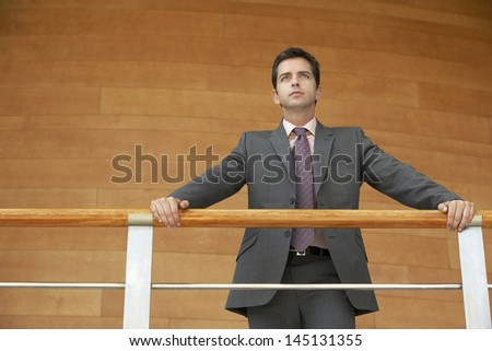 Low angle view of confident young businessman leaning on railing while standing against wooden wall - stock photo