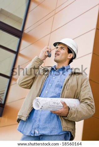 Low angle view of construction worker talking on cell phone and holding blueprints