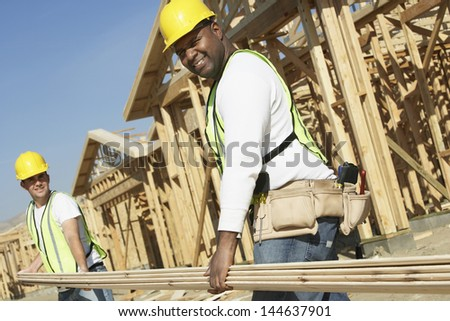 Low angle view of construction workers carrying boards at construction site - stock photo