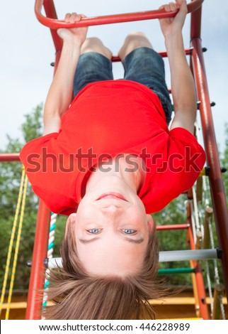Low angle view of cute teen boy wearing red tshirt hanging upside down from a climbing frame in a playground looking at camera smiling