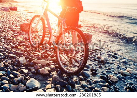 Low angle view of cyclist holding his bike. Man with bicycle on a sea shore sunset. Pebble beach coast. - stock photo