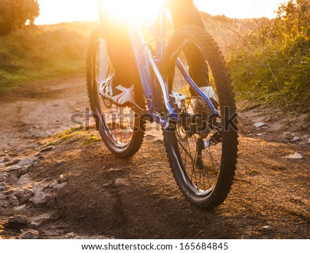 low angle view of cyclist riding mountain bike on rocky trail at sunrise - stock photo