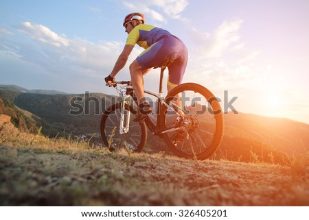 low angle view of cyclist standing with mountain bike on trail at sunset