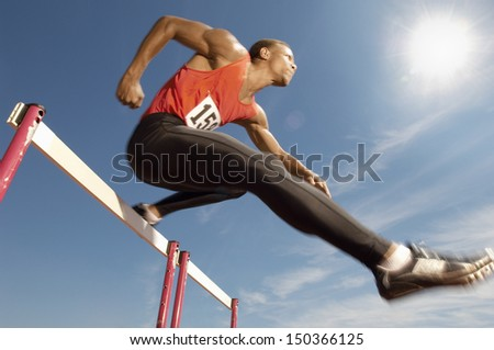 Low angle view of determined male athlete jumping over a hurdles - stock photo