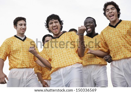 Low angle view of excited soccer players celebrating victory against sky