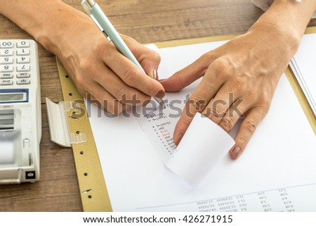 Low angle view of female accountant summing up the numbers writing on a printout receipt while making financial report. - stock photo