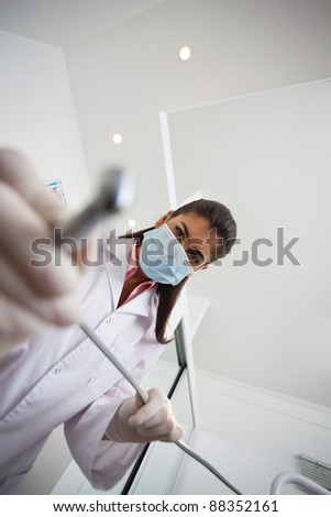 Low angle view of female dentist holding drill