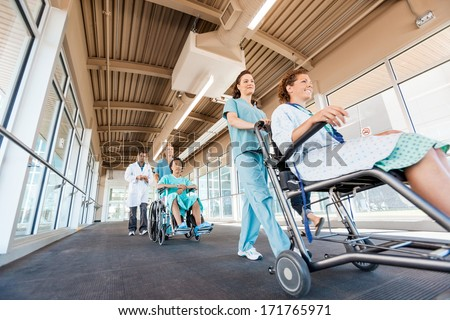 Low angle view of female nurses pushing patients on wheelchairs with doctor walking at corridor in hospital - stock photo