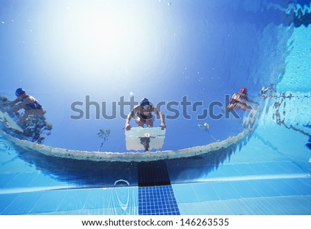 Low angle view of female swimmers ready to dive in pool from starting position - stock photo