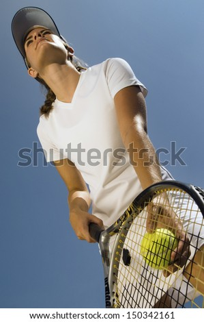 Low angle view of female tennis player holding ball and racket preparing to serve - stock photo