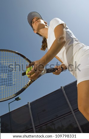 Low angle view of female tennis player ready for the shot - stock photo