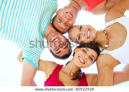 Low angle view of four friends embracing and looking at camera