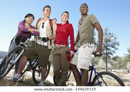 Low angle view of four multiethnic young friends standing on lake shore with mountain bikes - stock photo
