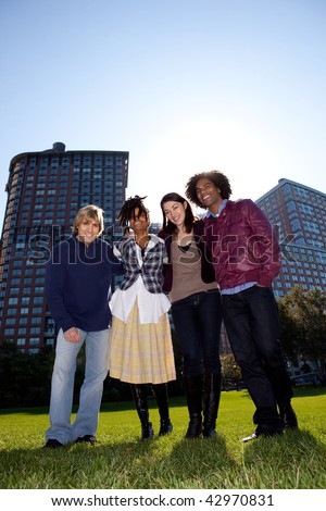 Low angle view of four people in urban park. Vertically framed shot. - stock photo
