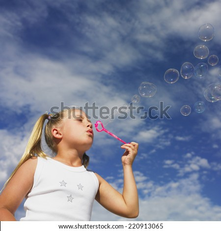 Low angle view of girl blowing bubbles