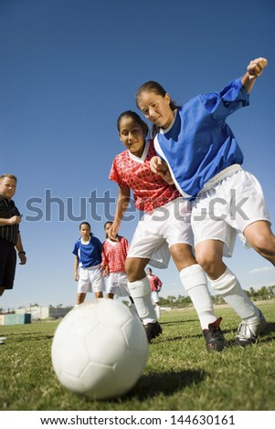 Low angle view of girls playing soccer - stock photo