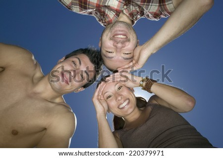 low angle view of group looking down and smiling - stock photo