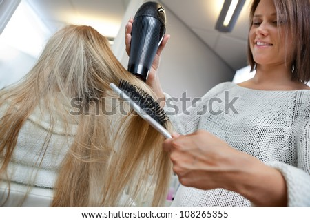 Low angle view of hairdresser drying long blond hair with blow dryer and brush - stock photo
