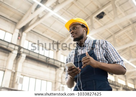 Low angle view of handsome African American machine operator wearing hardhat and overall listening to music on smartphone while standing at spacious production department of modern plant.