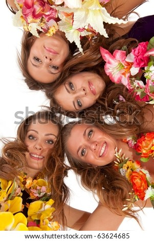Low angle view of happy beautiful hawaiian Hula Dancer Girls standing together in a circle - stock photo