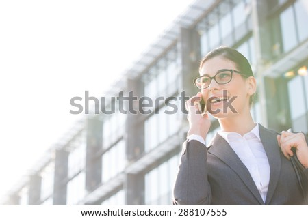 Low angle view of happy businesswoman using cell phone outside office building - stock photo