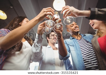 Low angle view of happy colleagues toasting with champagne in creative office - stock photo