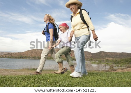 Low angle view of happy mother daughter and grand daughter walking by the lake - stock photo