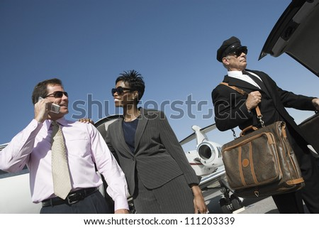 Low angle view of happy multiethnic business couple standing with driver holding luggage at airfield - stock photo