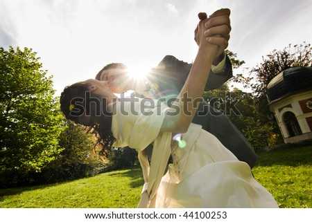 Low angle view of happy young newlywed couple dancing outdoors in sunlight.