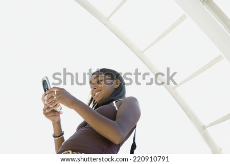 Low angle view of Indian woman dialing cell phone - stock photo