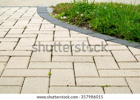 Low angle view of  light colored rectangular brick pavers in alternating pattern edged with dark grey pavers and grass.