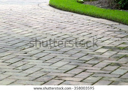 Low angle view of  light colored rectangular brick pavers in alternating pattern edged with grass. - stock photo