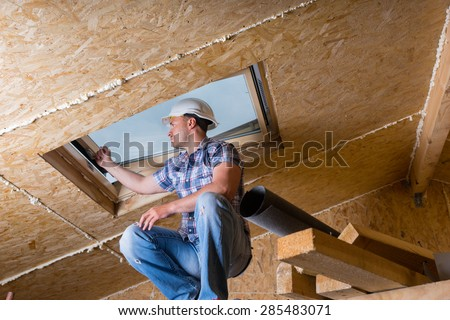 Low Angle View of Male Construction Worker Builder Crouching on Elevated Scaffolding near Ceiling and Inspecting Frame of Sky Light Window in Unfinished House with Exposed Particle Plywood Board - stock photo