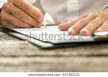 Low angle view of male hand signing contract or subscription form with a pen on a rustic wooden desk. - stock photo