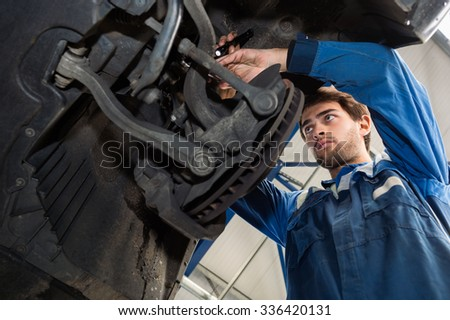 Low angle view of male mechanic repairing car in automobile shop - stock photo