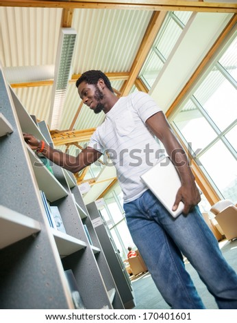 Low angle view of male student with digital tablet choosing book in bookstore - stock photo