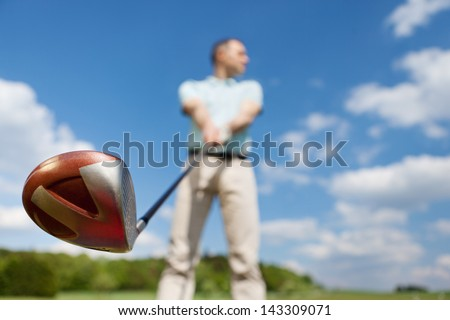 Low angle view of man holding golf club against sky - stock photo