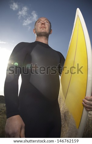 Low angle view of man in wetsuit carrying surfboard on beach - stock photo