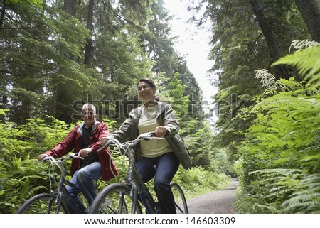 Low angle view of mature man and middle aged woman with bikes on forest road - stock photo