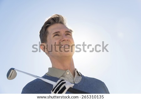 Low angle view of mature man holding golf club against sky - stock photo