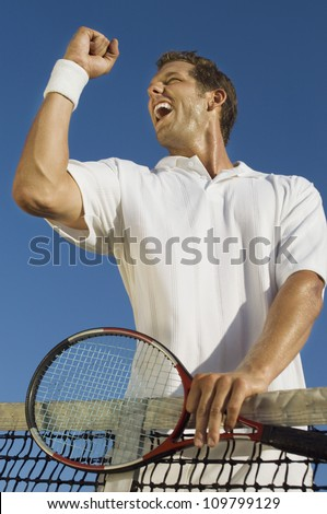 Low angle view of mid adult male tennis player celebrating success