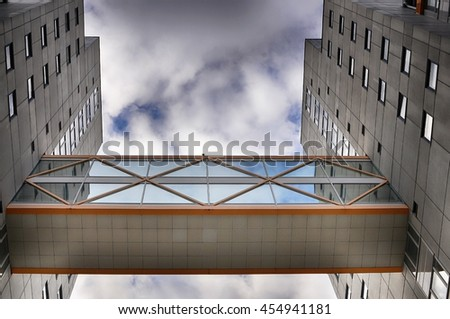 Low angle view of modern concrete buildings with overpass in between. - stock photo